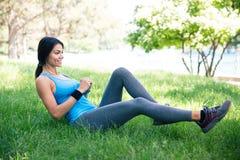 Donna sportiva che fa allungando i exercsises in parco Fotografia Stock