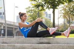 Donna sportiva che fa gli allungamenti prima dell'esercitazione nel parco Immagini Stock Libere da Diritti