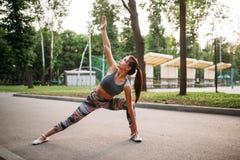 Donna sportiva che fa gli esercizi di forma fisica in parco Immagini Stock Libere da Diritti
