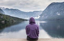 Donna sportiva che guarda scena nuvolosa tranquilla di mattina nel lago Bohinj, montagne delle alpi, Slovenia Immagini Stock Libere da Diritti
