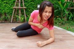 Donna sportiva che ha attacco di cuore e che cerca qualcuno aiuto - Fotografia Stock