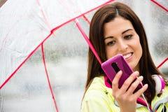 Donna sportiva che manda un sms sullo smartphone all'aperto Immagini Stock