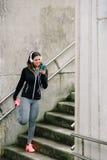 Donna sportiva che manda un sms sullo smartphone e sull'allungamento Fotografia Stock