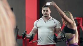Donna sportiva che prende selfie con l'uomo forte che risolve nella palestra video d archivio