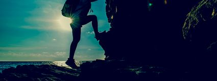 Donna sportiva che scala sulla scogliera immagini stock