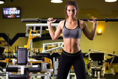 Donna sportiva che si esercita con il bilanciere in palestra immagine stock