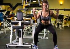 Donna sportiva che si esercita con il bilanciere in palestra fotografia stock