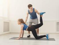 Donna sportiva che si esercita con il suo istruttore personale Fotografia Stock Libera da Diritti
