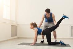 Donna sportiva che si esercita con il suo istruttore personale Immagini Stock Libere da Diritti