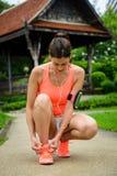 Donna sportiva che si prepara per correre al parco della città Immagine Stock