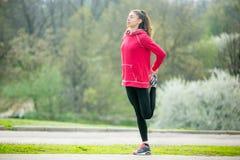 Donna sportiva che si scalda all'aperto Immagini Stock Libere da Diritti