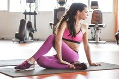 Donna sportiva che si siede sulla stuoia di yoga che fa allungamento della gamba Immagini Stock