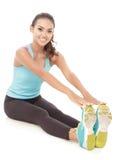 Donna sportiva che sorride mentre facendo allungamento del corpo Fotografie Stock