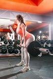 Donna sportiva con il bilanciere che esamina specchio Fotografia Stock