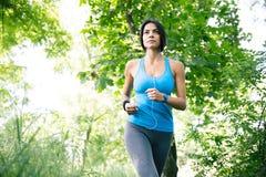 Donna sportiva in cuffie che corre all'aperto Immagine Stock