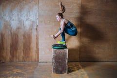 Donna sportiva del yuong di misura che salta sopra l'alta scatola durante l'allenamento di forma fisica, vista laterale Fotografia Stock Libera da Diritti