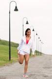 Donna sportiva di forma fisica che allunga le gambe prima dell'correre Fotografia Stock Libera da Diritti