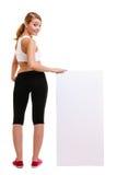 Donna sportiva di forma fisica che tiene banner pubblicitario vuoto in bianco Fotografia Stock