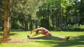 Donna sportiva di misura che esercita e che allunga il suo corpo video d archivio