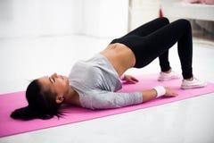 Donna sportiva di posa del ponte che fa scaldandosi esercizio Immagini Stock