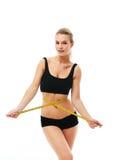 Donna sportiva e misura intorno al suo corpo su fondo bianco Fotografie Stock Libere da Diritti