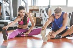 Donna sportiva ed uomo che fanno allungamento della gamba Immagine Stock