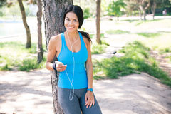 Donna sportiva felice che sta con lo smartphone all'aperto immagini stock