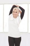 Donna sportiva musulmana bella che fa allungamento della mano Immagini Stock