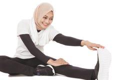 Donna sportiva musulmana che fa allungamento della gamba Immagini Stock Libere da Diritti
