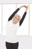 Donna sportiva musulmana che fa allungamento della mano Fotografia Stock