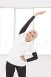 Donna sportiva musulmana che fa allungamento della mano e del corpo Fotografie Stock Libere da Diritti