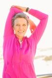 Donna sportiva sorridente che allunga armi alla passeggiata Immagini Stock