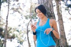 Donna sportiva sorridente che per mezzo dello smartphone all'aperto fotografia stock libera da diritti