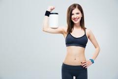 Donna sportiva sorridente con il barattolo di proteina fotografie stock libere da diritti