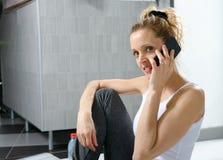Donna sportiva sveglia che per mezzo del suo smartphone Immagini Stock