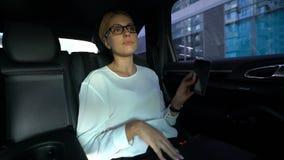 Donna stanca che fa un pisolino, sedendosi sul sedile posteriore dell'automobile, andante ad incontrare i partner archivi video