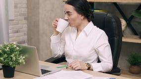 Donna stanca che lavora in ufficio e caffè bevente stock footage