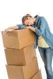 Donna stanca che riposa sulle scatole di cartone impilate Fotografia Stock Libera da Diritti