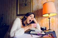 Donna stanca che sbadiglia e che lavora a casa immagini stock libere da diritti