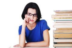 Donna stanca che si siede ad uno scrittorio con la pila di libri Immagine Stock