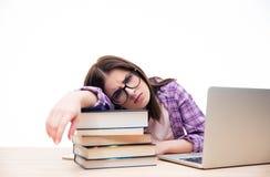 Donna stanca che si siede alla tavola con il computer portatile Fotografie Stock Libere da Diritti