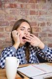 Donna stanca che si siede alla tavola con il suo compito Immagini Stock Libere da Diritti