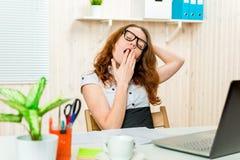 Donna stanca di affari che sbadiglia e che allunga al suo scrittorio Fotografia Stock Libera da Diritti
