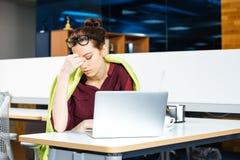 Donna stanca di affari nel funzionamento di vetro con il computer portatile sul posto di lavoro Fotografia Stock