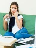 Donna stanca dietro il suo computer portatile Immagine Stock Libera da Diritti
