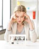 Donna stanca dietro la tavola con i hourgalss Fotografia Stock