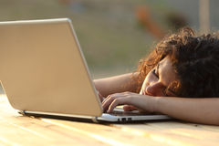 Donna stanca sovraccarica che riposa sopra un computer portatile immagini stock libere da diritti