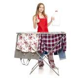 Donna in stendipanni dei vestiti del grembiule con la bottiglia di plastica dei vestiti puliti per il detersivo di lavanderia liq fotografie stock libere da diritti
