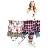 Donna in stendipanni dei vestiti del grembiule con la bottiglia di plastica dei vestiti puliti per il detersivo di lavanderia liq immagini stock