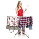 Donna in stendipanni dei vestiti del grembiule con la bottiglia di plastica dei vestiti puliti per il detersivo di lavanderia liq fotografia stock